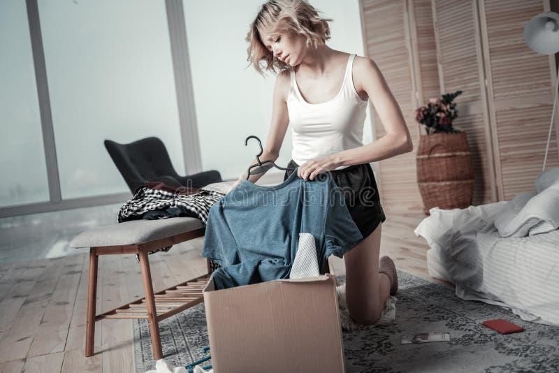 Roupa de embalagem da jovem mulher magro do noivo ex em caixas imagens de stock