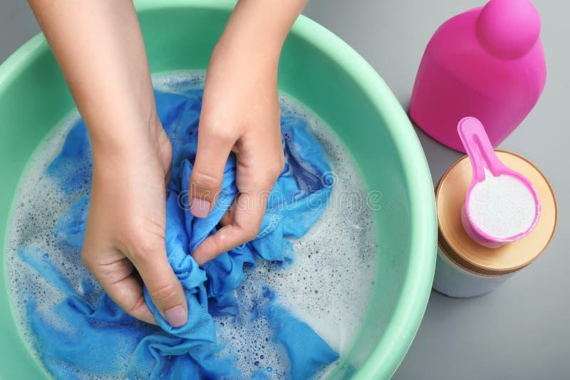 Roupa de lavagem da cor da mulher na bacia foto de stock royalty free