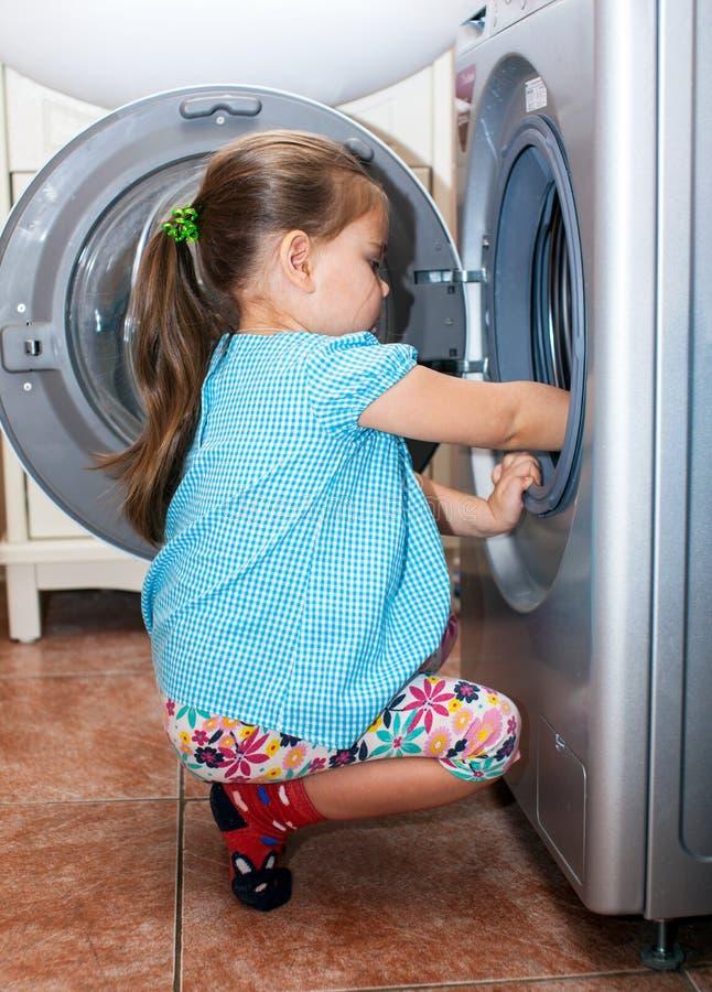 Roupa de lavagem da menina na máquina imagem de stock royalty free