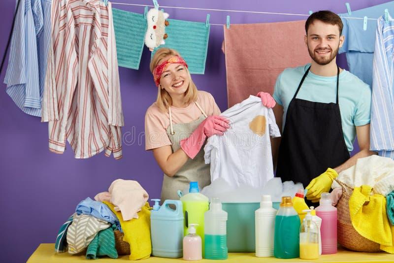 Roupa de lavagem do louro feliz e do homem farpado considerável à mão imagens de stock royalty free