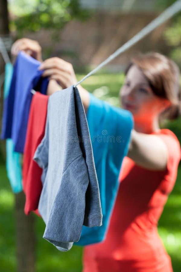 Roupa de suspensão da mulher na linha da lavanderia no jardim imagens de stock royalty free