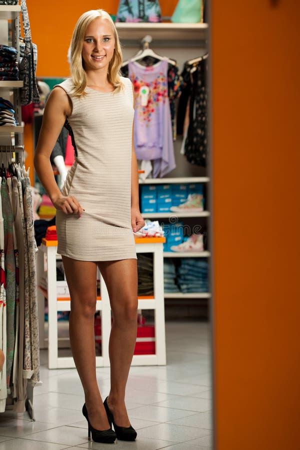 Roupa de tentativa da mulher em um lookung da loja de roupa seu auto no imagem de stock royalty free