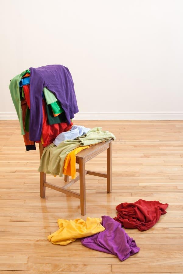 Roupa desarrumado colorida em uma cadeira foto de stock royalty free