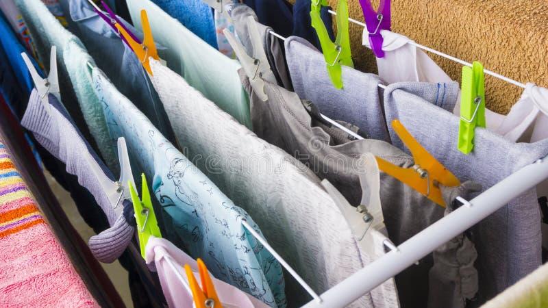 Roupa diferente que pendura com os pinos coloridos no clotheshorse para secar no balcão fotografia de stock royalty free