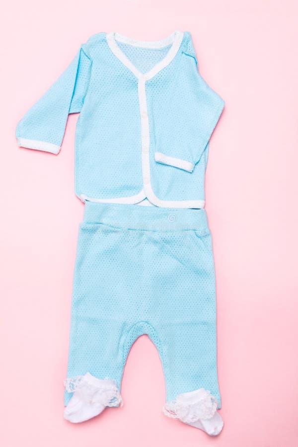 Roupa do bebê azul no fundo cor-de-rosa com camisa, calças e as peúgas brancas no fundo cor-de-rosa Forma do verão do projeto da  imagem de stock
