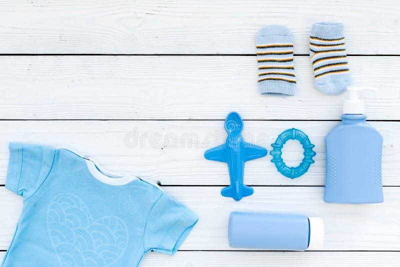 Roupa do bebê azul para o rapaz pequeno Bodysuit, brinquedos, cosméticos no espaço de madeira branco da cópia da opinião superior imagem de stock royalty free
