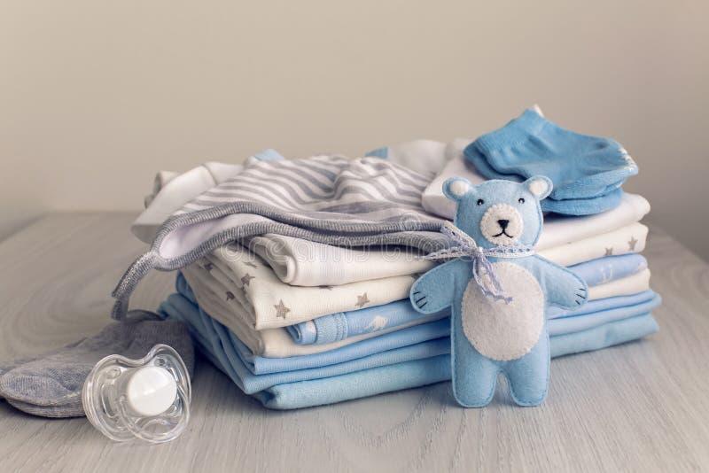 A roupa do bebê com tecidos é empilhada foto de stock royalty free