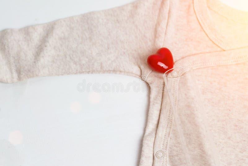 Roupa do bebê com tubo de ensaio e coração Conceito - IVF, in vitro fecundação Bebê de espera, grávido imagem de stock royalty free