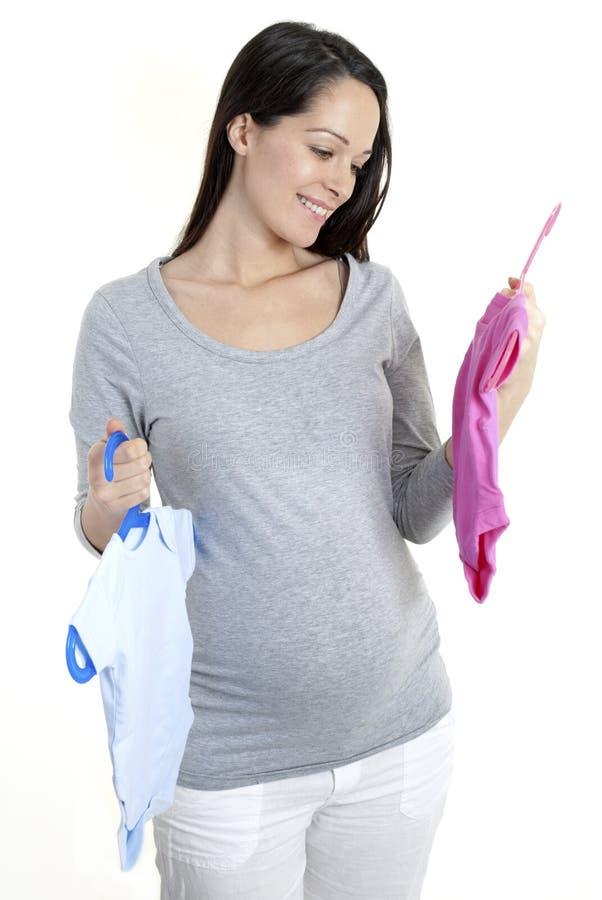 Roupa do bebê da terra arrendada da mulher gravida imagem de stock