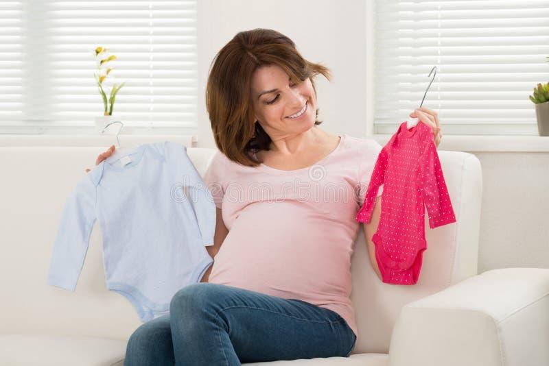 Roupa do bebê da terra arrendada da mulher gravida fotos de stock royalty free