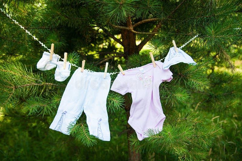 Roupa do bebê que pendura na corda imagens de stock
