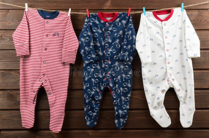 Roupa do bebê & x28; sleepsuits& x29; suspensão na corda foto de stock royalty free