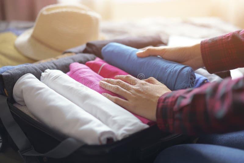 A roupa do bloco da mulher no saco da mala de viagem na cama, prepara-se para a viagem nova fotografia de stock