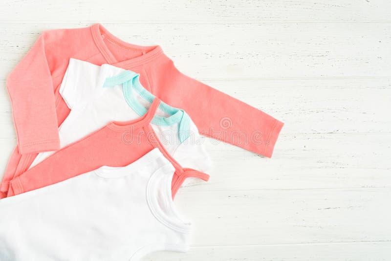 Roupa do bodysuit do bebê sobre o fundo de madeira branco Copie o espa?o estilo liso da configura??o foto de stock royalty free