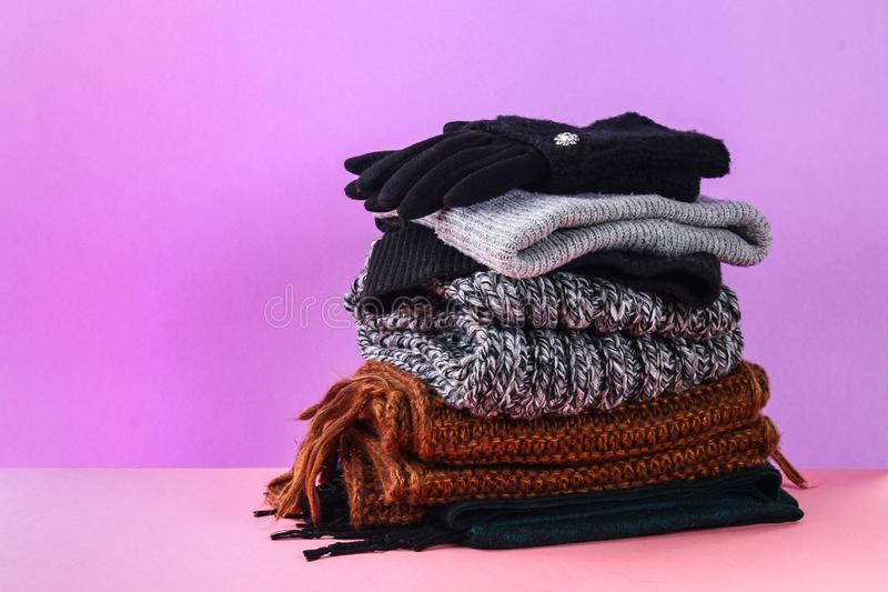 Roupa do inverno e do outono, chapéus, scarves, luvas em um fundo pastel roxo fotos de stock