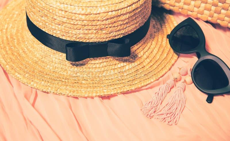 Roupa e acess?rios da mulher Chap?u de palha, ?culos de sol na moda pretos, brincos e fragmento de um vestido e de um saco colori fotografia de stock royalty free