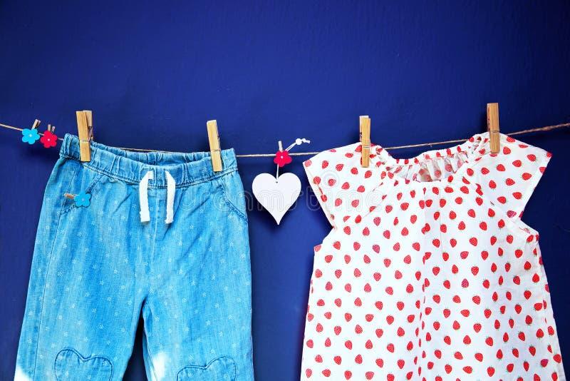 Roupa e bens do bebê que penduram na corda fotos de stock