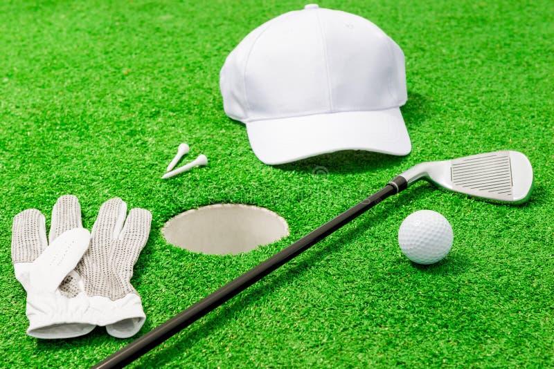 Roupa e ferramentas para o jogo do golfe perto do furo imagem de stock