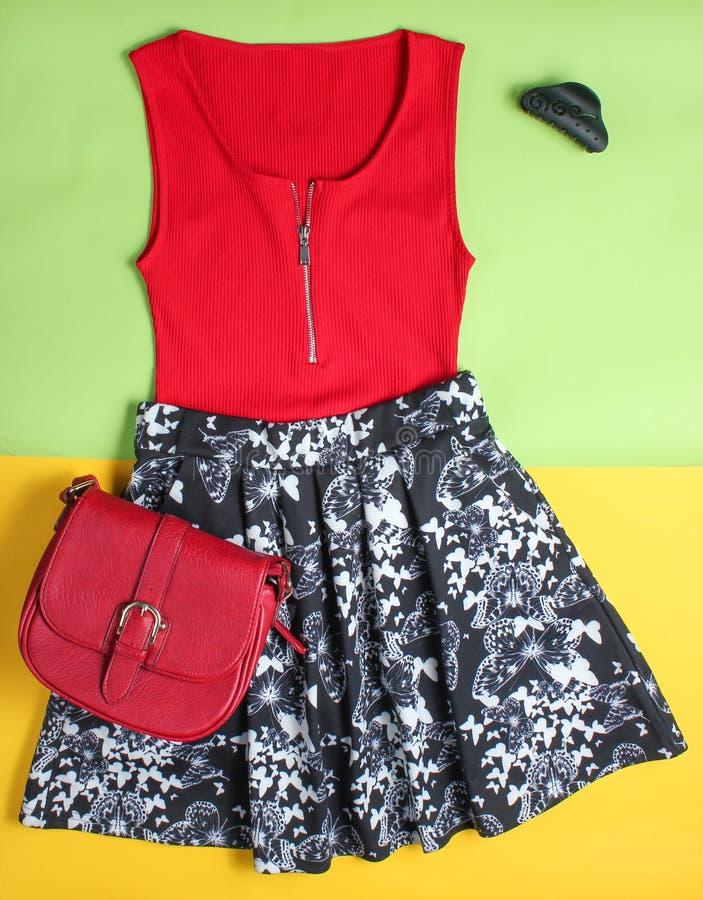 A roupa e os acessórios das mulheres em um fundo colorido Saia, t-shirt, saco de couro, grampo de cabelo, vista superior foto de stock