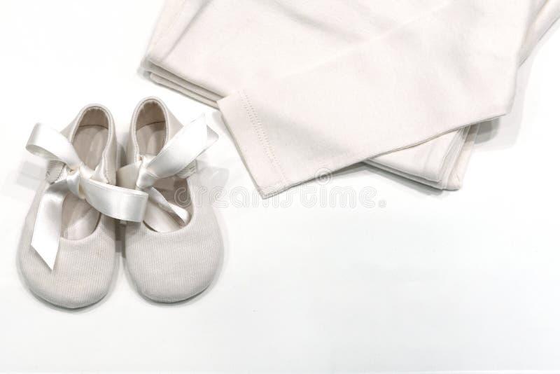 Roupa e sapatas do bebê para bebês das telas naturais Vista superior das sapatas com laços e da camisa para a cor bege do bebê qu imagem de stock