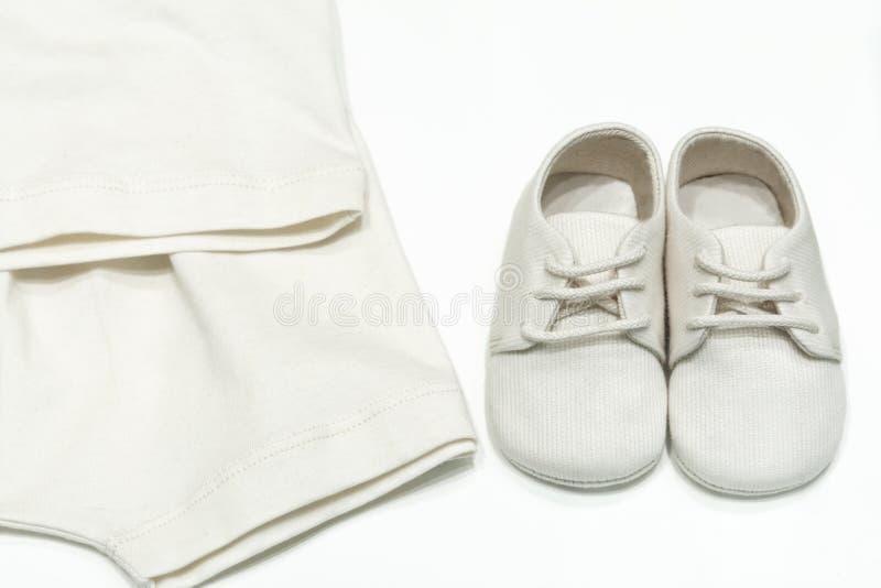 Roupa e sapatas do bebê para bebês das telas naturais Vista superior das sapatas em laços e dos bodysuits para a cor bege do bebê fotos de stock