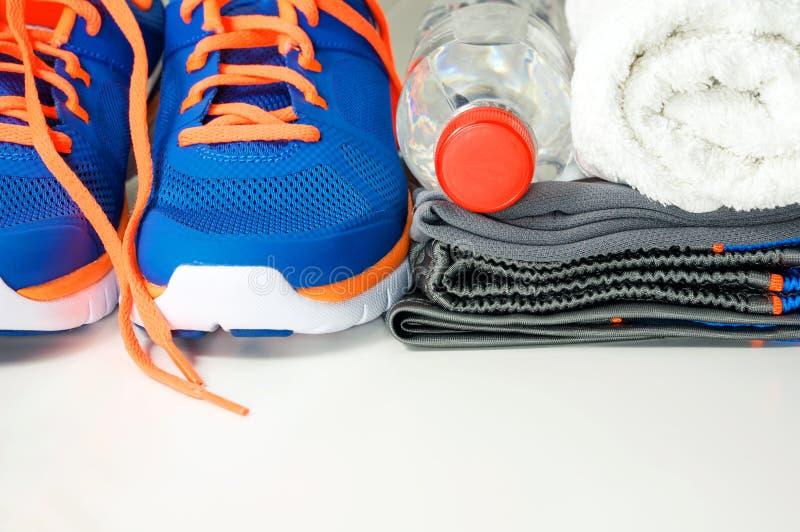 Roupa e sapatas do esporte com água potável fotografia de stock
