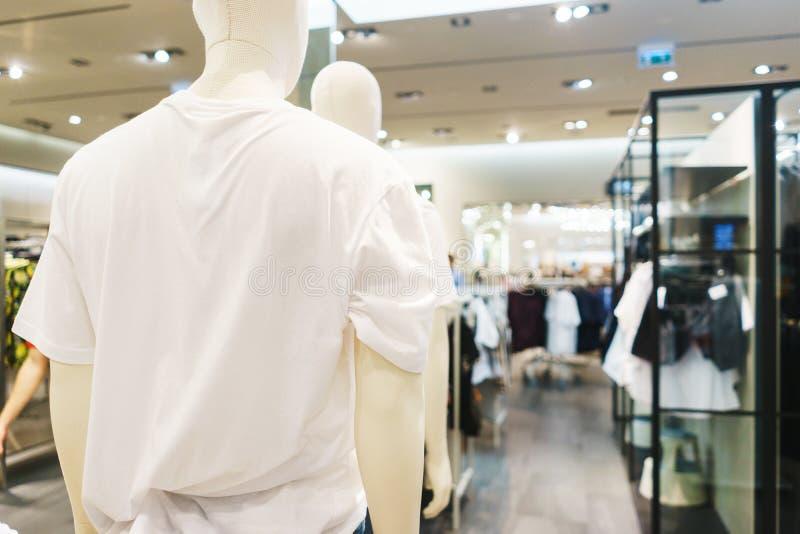 Roupa elegante brilhante dos ganchos T-shirt, blusas e camisas em um gancho no close-up da alameda fotografia de stock