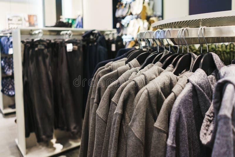 Roupa elegante brilhante dos ganchos T-shirt, blusas e camisas em um gancho no close-up da alameda foto de stock royalty free