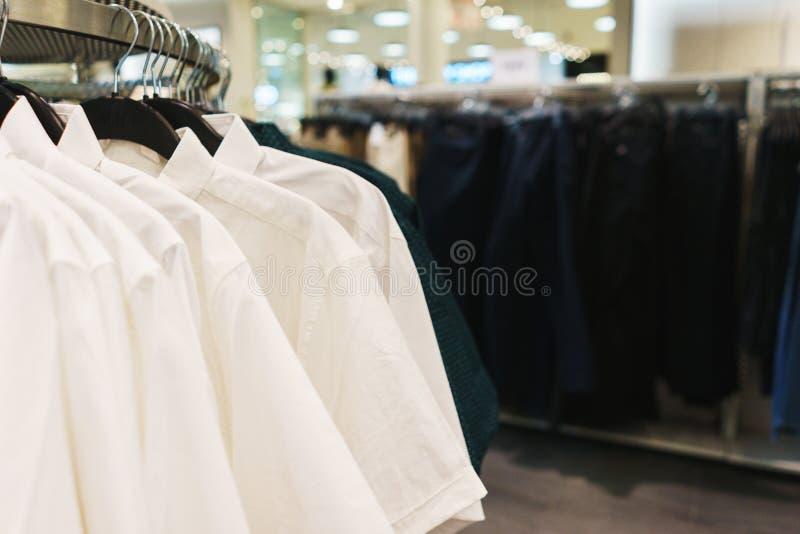 Roupa elegante brilhante dos ganchos T-shirt, blusas e camisas em um gancho no close-up da alameda fotografia de stock royalty free
