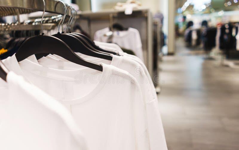 Roupa elegante brilhante dos ganchos T-shirt, blusas e camisas em um gancho no close-up da alameda fotos de stock royalty free