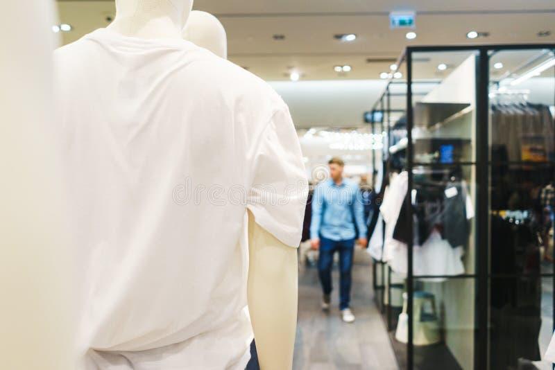 Roupa elegante brilhante dos ganchos T-shirt, blusas e camisas em um gancho no close-up da alameda imagens de stock