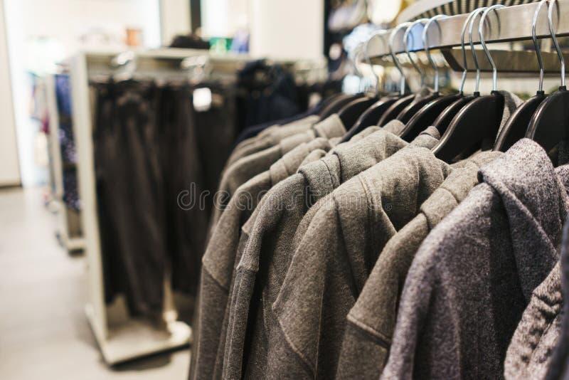 Roupa elegante brilhante dos ganchos T-shirt, blusas e camisas em um gancho no close-up da alameda fotos de stock