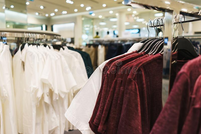 Roupa elegante brilhante dos ganchos T-shirt, blusas e camisas em um gancho no close-up da alameda imagem de stock royalty free