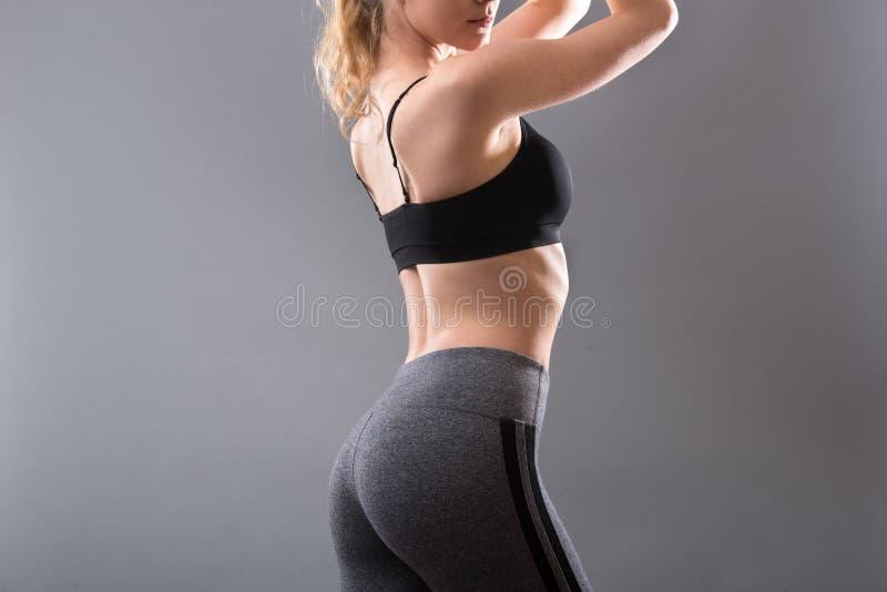 Roupa fêmea do sportswear no corpo perfeito Sutiã do esporte e calças cinzentas dos leggins imagens de stock