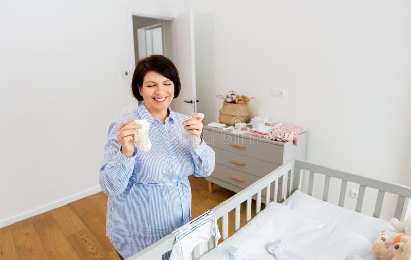 Roupa feliz do beb? do ajuste da mulher gravida em casa imagens de stock