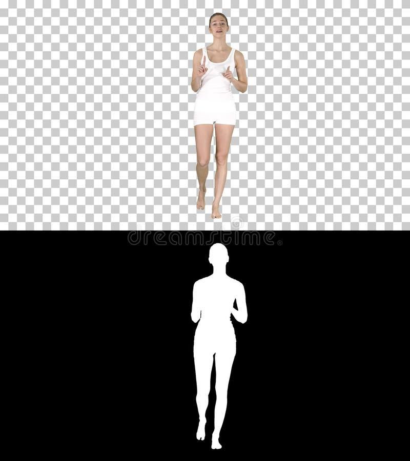 Roupa interior branco vestindo da mulher bonita que anda e que fala à câmera, Alpha Channel fotografia de stock