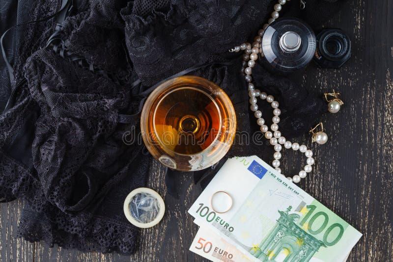 Roupa interior, conhaque e dinheiro para simbolizar o custo do sexo fotografia de stock