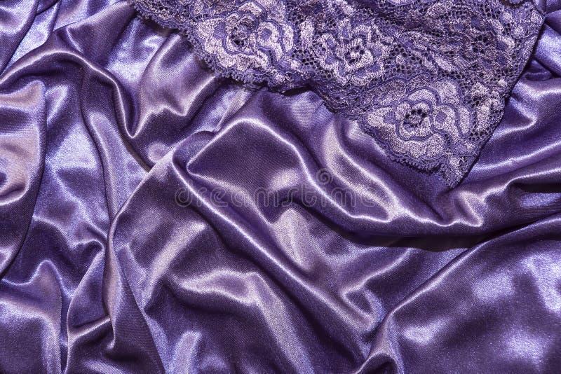Roupa, roupa interior Fundo roxo do cetim de seda elegante do sumário com destaques com uma textura macia da tela com uma meia d foto de stock royalty free