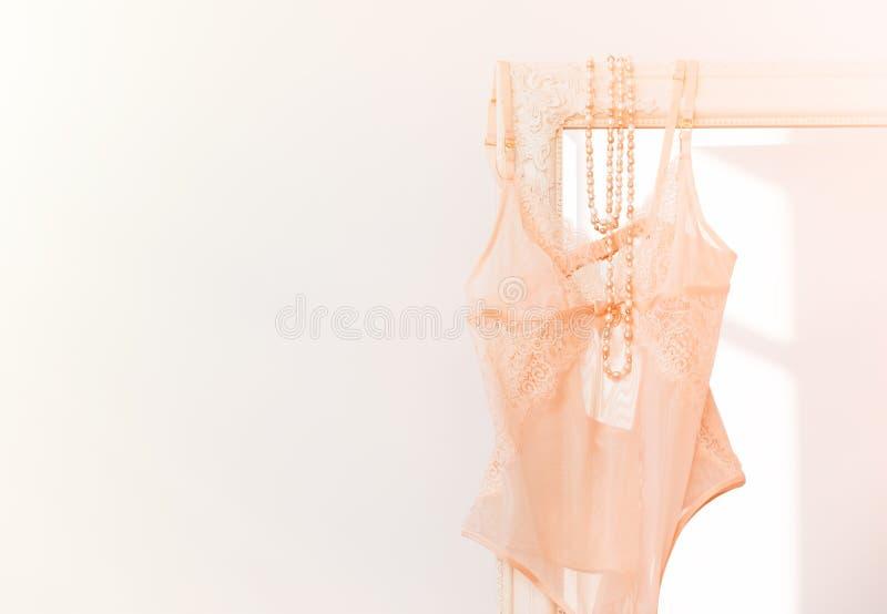 Roupa interior 'sexy' bege do bodysuit do ` s da mulher que pendura no espelho imagem de stock royalty free