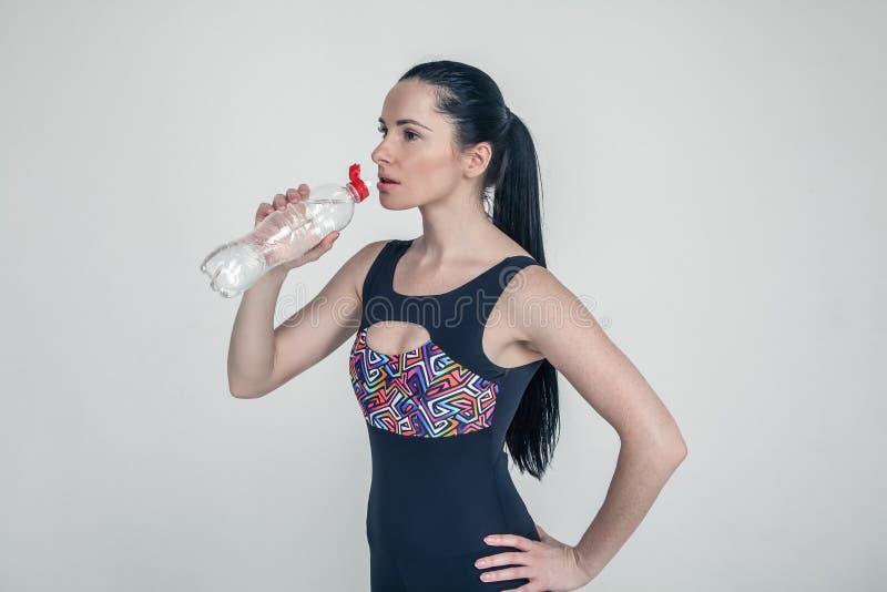 Roupa moreno magro bonita dos esportes da moça no fundo cinzento Água potável modelo saudável desportiva da garrafa a ficar foto de stock royalty free