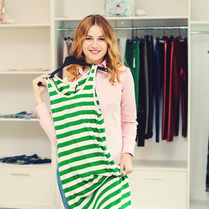 Roupa na moda de compra da menina bonita Forma da mulher Mulher feliz que escolhe a roupa na loja de roupa Vendas sazonais Fazer  foto de stock royalty free