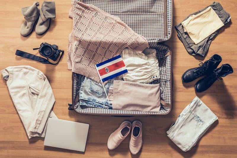 A roupa, o portátil, a câmera e a bandeira da mulher de Costa Rica encontrando-se no assoalho de parquet perto e na mala de viage fotos de stock royalty free