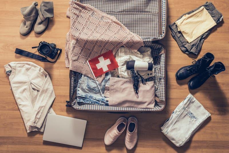 A roupa, o portátil, a câmera e a bandeira da mulher de Suíça encontrando-se no assoalho de parquet perto e na mala de viagem abe foto de stock royalty free