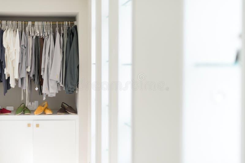 Roupa ocasional em ganchos e em sapatas na loja. imagem de stock