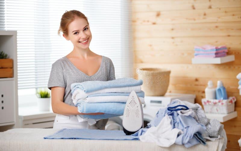 Roupa passando da dona de casa feliz da mulher na lavanderia em casa fotos de stock