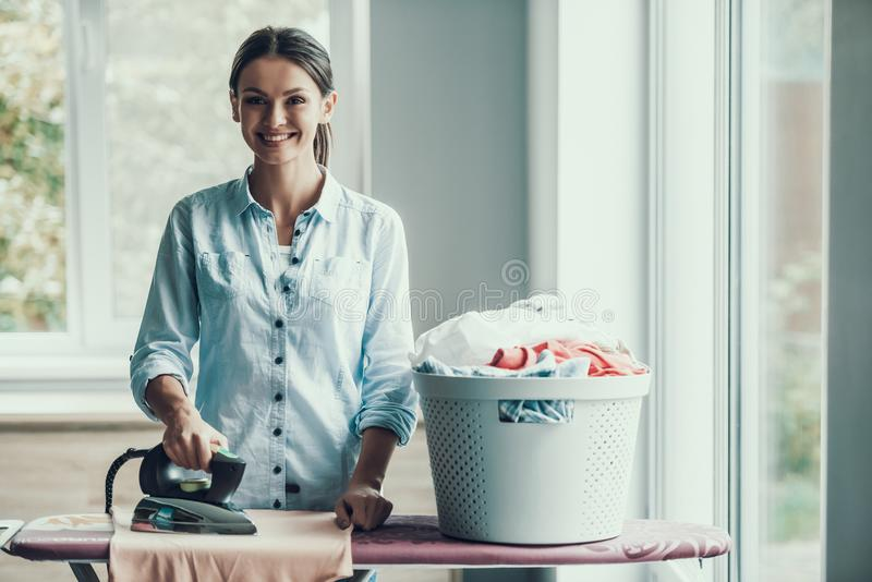 Roupa passando de sorriso nova da mulher após a lavanderia foto de stock