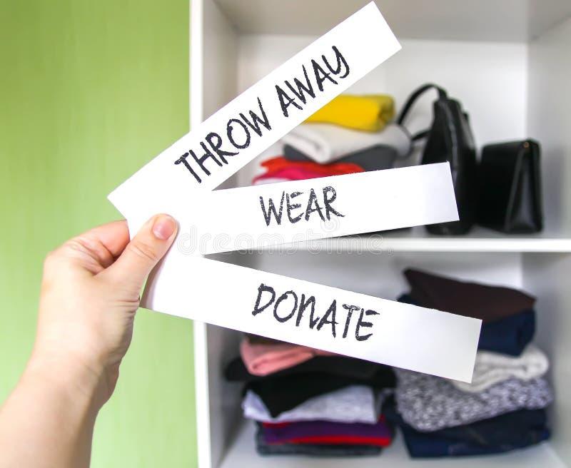 Roupa que classifica no vestuário da casa para a doação, vestir e o descarte Vista, doe e jogue afastado as notas de papel em uma imagens de stock