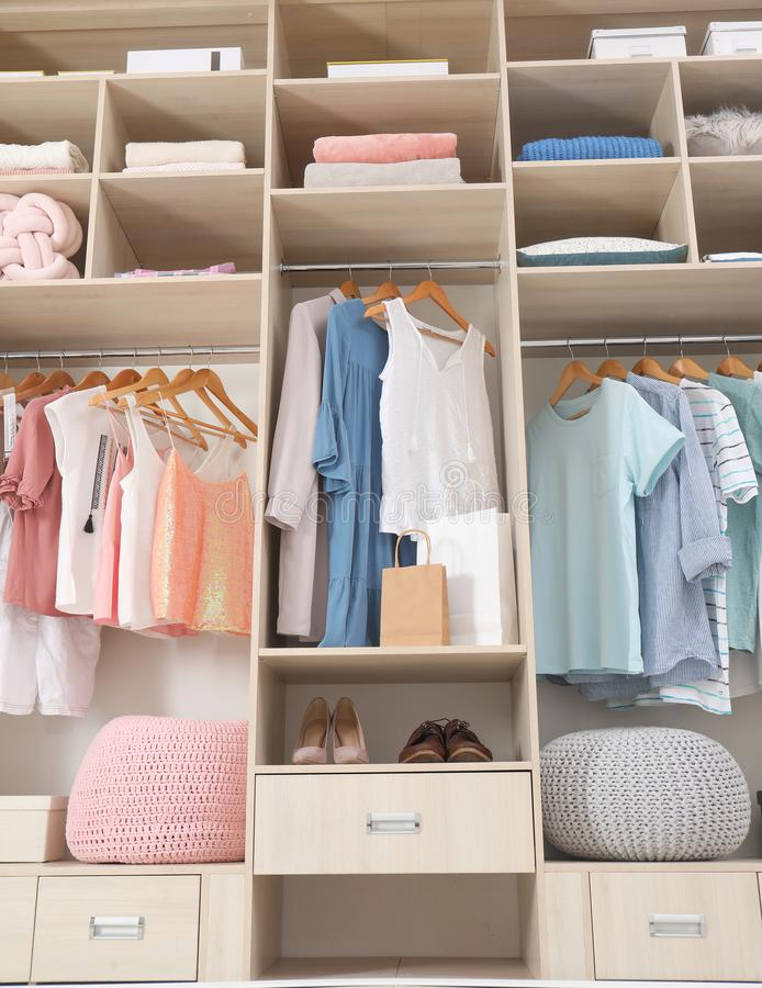 Roupa, sapatas e acessórios à moda no grande armário do vestuário fotos de stock