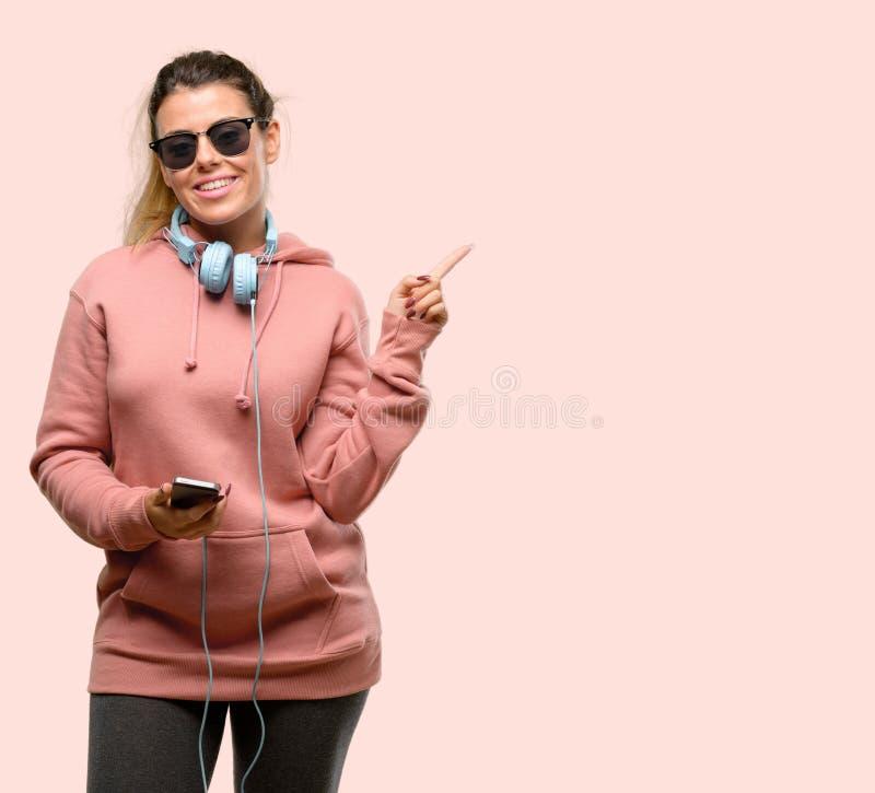 Roupa vestindo do esporte da jovem mulher sobre o fundo cor-de-rosa imagens de stock royalty free