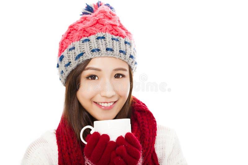 Roupa vestindo do inverno da mulher bonita e guardar o copo de café foto de stock royalty free